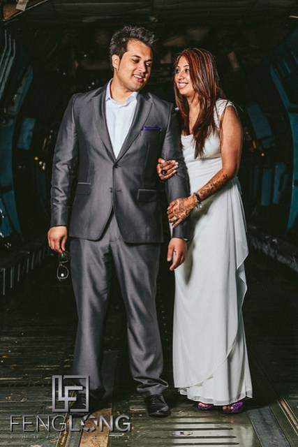 Indian bride and groom posing for pre-wedding photos inside airplane cargo bay