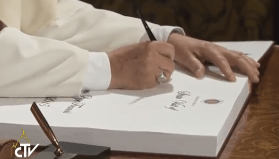 Pope Francis signs the guest book