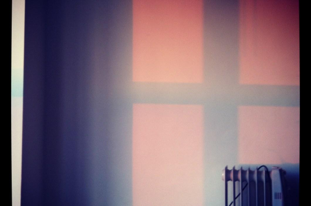 Foto de la sombra de una ventana en una pared con radiador