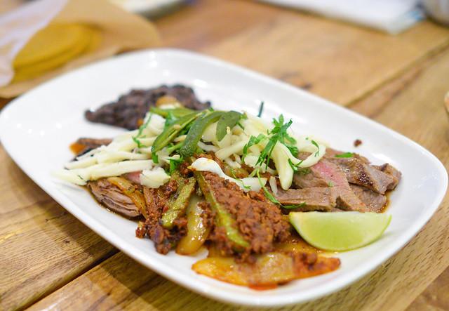 Carne Asada con Chorizo y Nopales Grilled marinated sirloin steak, house made red chorizo,seared cactus, jalapeño, onion, refried black beans, Oaxacan cheese and salsa pasilla