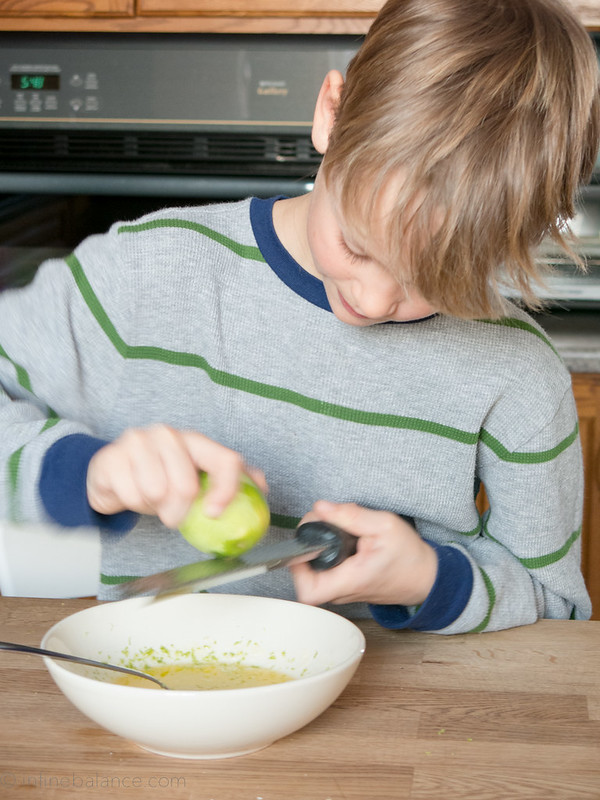 grating lime zest into bowl of lime butter sauce