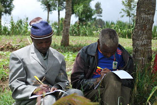 Gabriel Sikay (right) and a fellow farmer take notes during the on-farm training on forage data collection and soil water management (Photo credit: IITA/Gloriana Ndibalema)