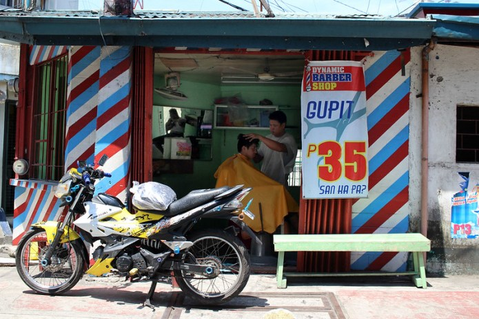 barbershop with a motorcycle parked in front of it