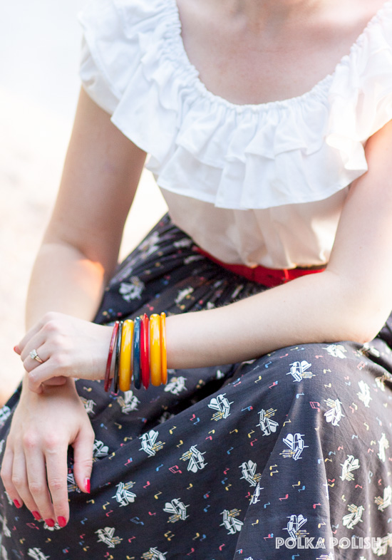 Bakelite bangles in red, yellow, and blue bring out the colors in a vintage 1950s novelty print skirt with a musical theme