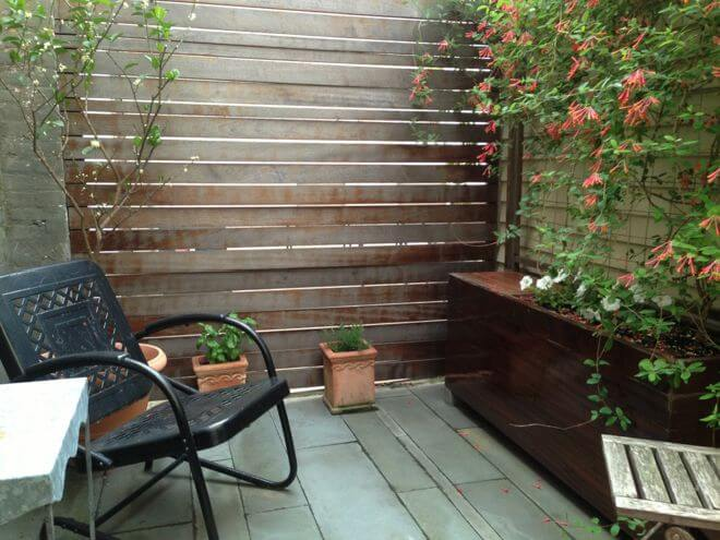 Trellises, narrow planting beds and containers are good ways to bring life and height to a small walled-in patio.