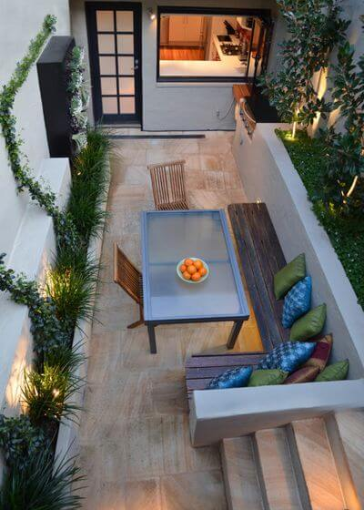 For this long, narrow patio, a long, narrow dining table and built-in benches are just the right fit.