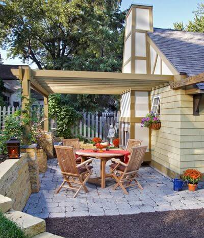 Patios typically are located off the house, but if you don't have room to expand there, a detached garage or shed can provide a nice anchor for an outdoor living space. Here, a wood-burning fireplace and window boxes off the garage add warmth and charm to the patio, and the structure also provides a place to anchor a pergola.