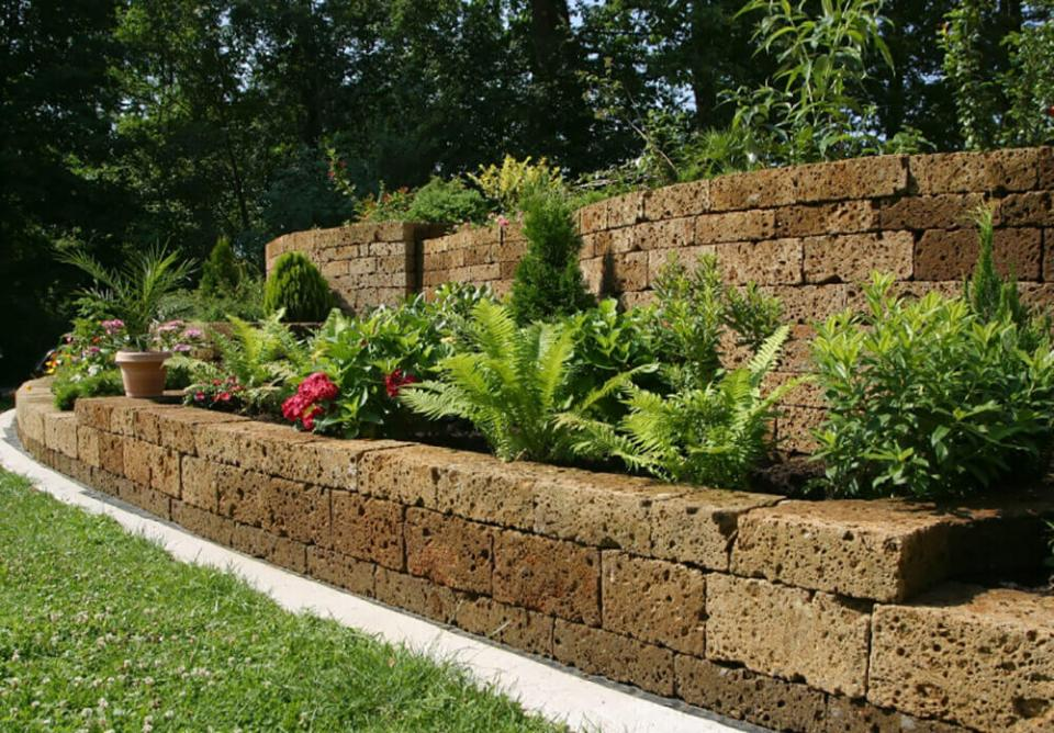 Bushes line the raised garden bed against the stone wall