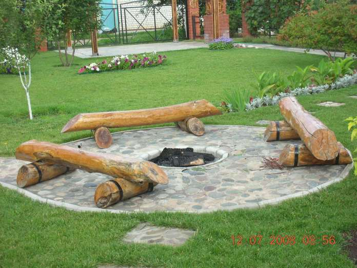 Log Benches Surrounding a Pit in Stone | Awesome Firepit Area Ideas For Your Outdoor Activities