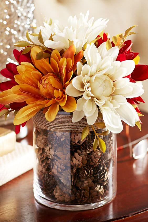 A glass vase filled with pinecones | Best Thanksgiving Centerpieces