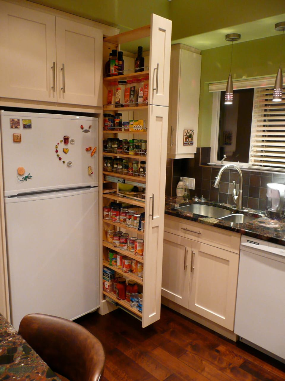 The narrow cabinet beside the fridge pulls out to reveal a spice & canned goods pantry