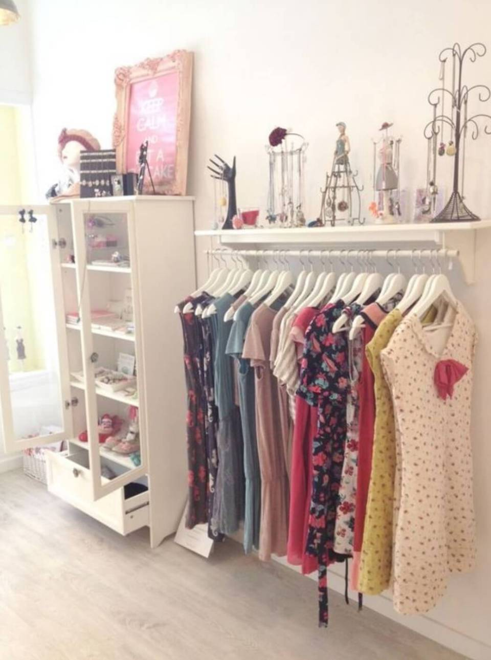Wardrobe made with a wooden shelf and a low tube fixing to the wall with hanging dresses.