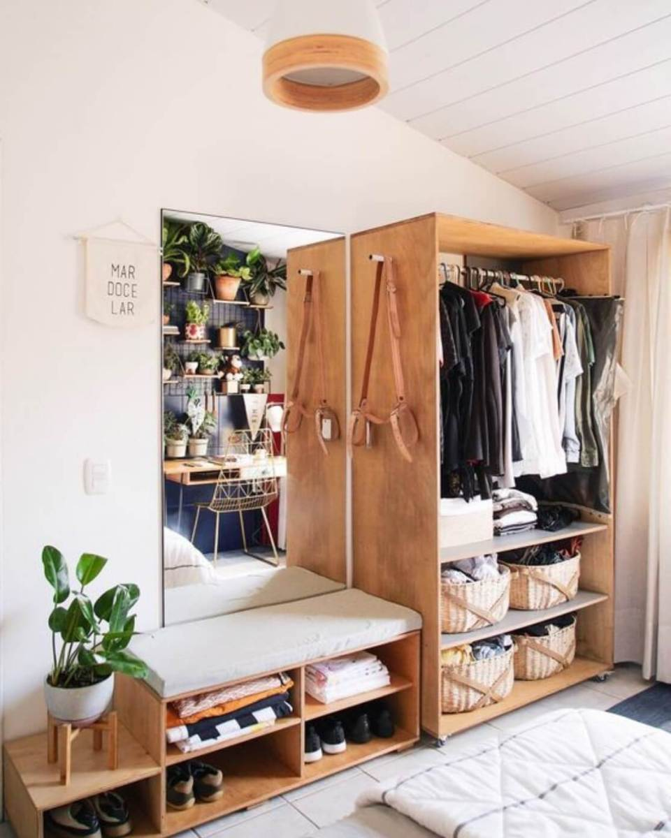 Bedroom with wooden table and closet full of clothes