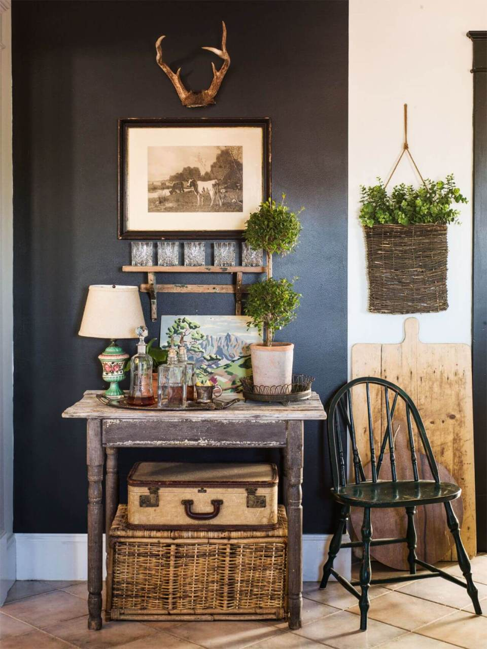 Dark accent wall, old table with topiary plants
