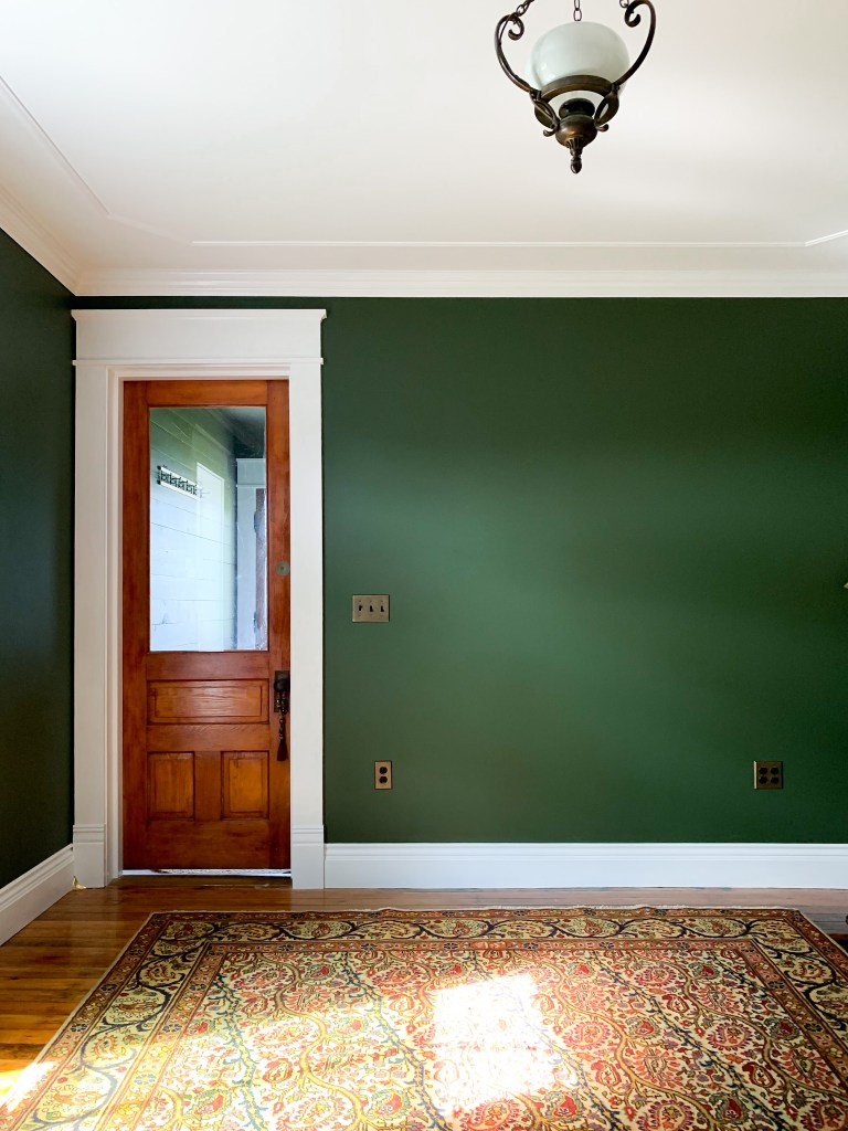 green room with orange door and rug