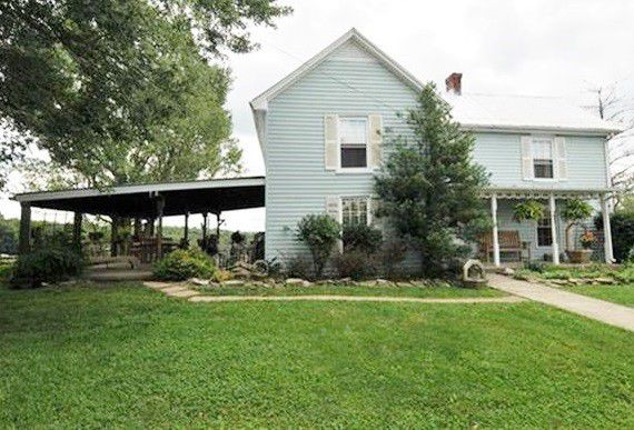 blue farmhouse with overgrown landscaping and large side porch