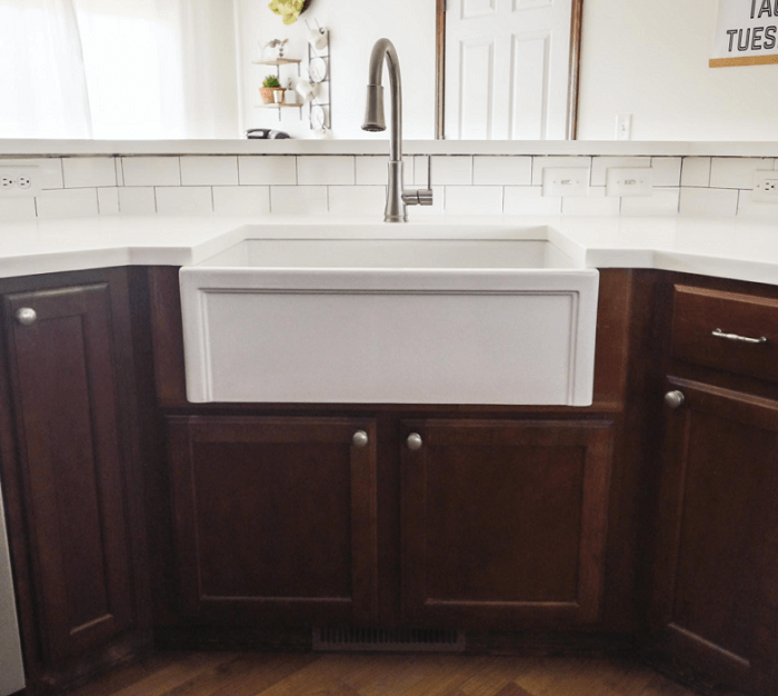 a farmhouse sink in existing cabinets