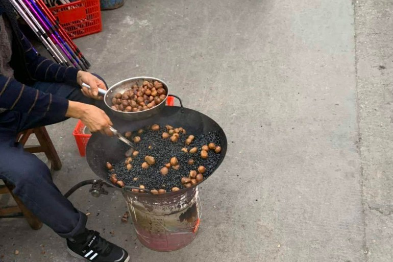 Man roasting cashew nuts at a Chinese market