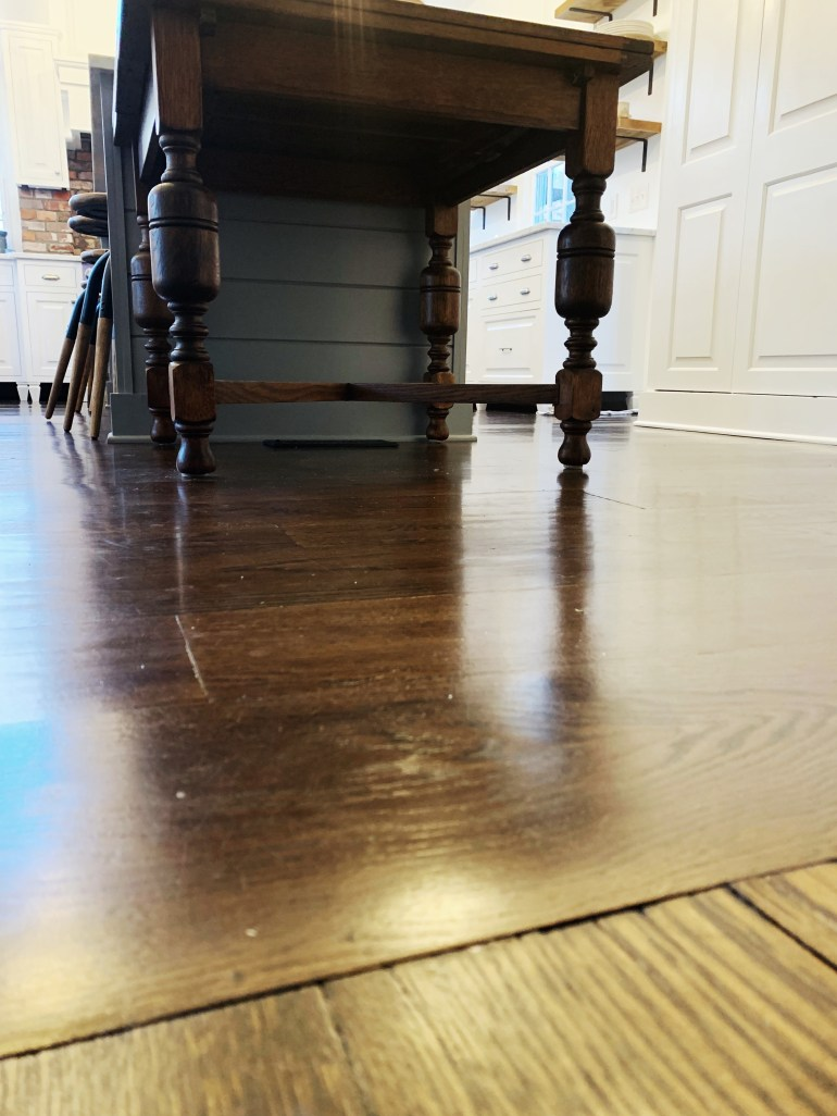 Kitchen table at the end of a gray island and wide plank floors