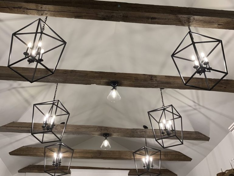 Black iron cage lights against a cathedral ceiling with reclaimed beams