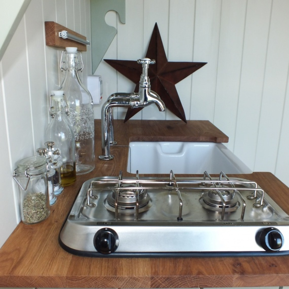 A small kitchen unit in The Pleasant Pheasant with belfast sink and 2 ring gas hob with a metal star decoration in background
