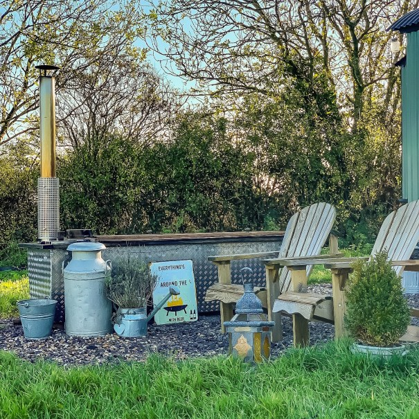 Outside The Pleasant Pheasant A Swedish Hikki Bohemen wood burning hot tub sits by a hedge next to some Adirondack chairs