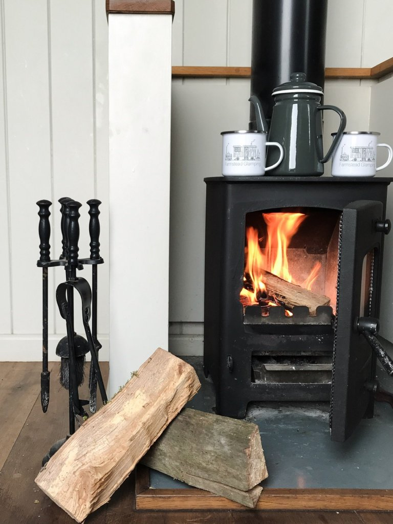 An enticing small wood burning stove is lit with a enamel coffee pot and mugs on top