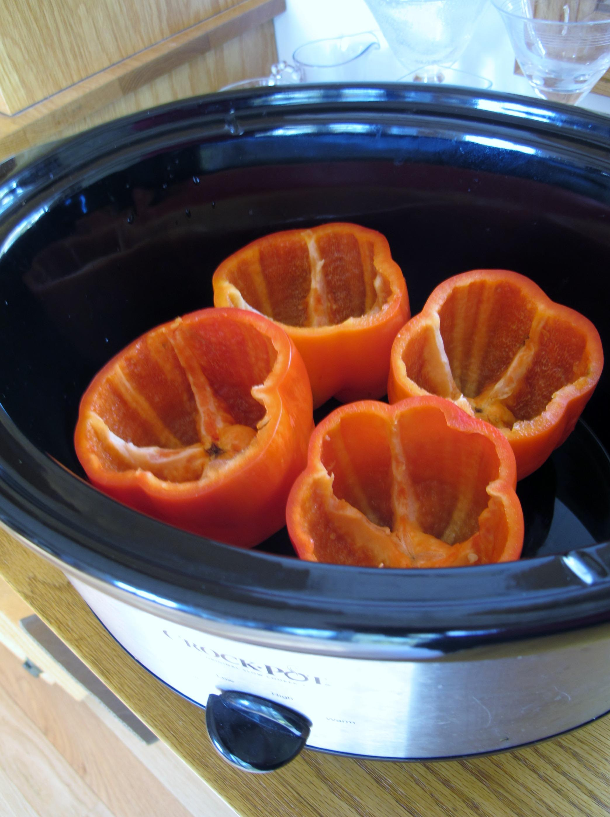 Red bell eppers in crock pot ready for stuffing