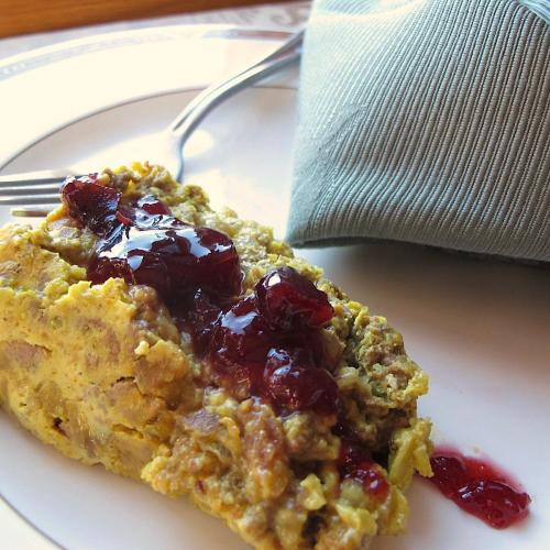 Slice of bobotie with cranberry chutney topping
