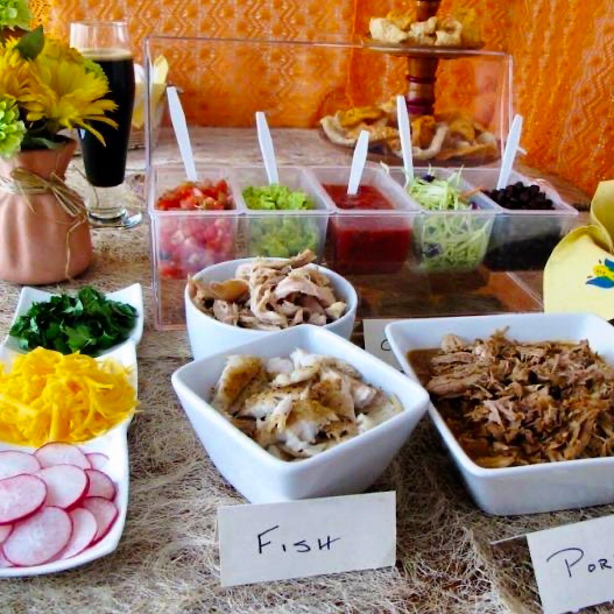 A table of various taco fixings for a taco bar