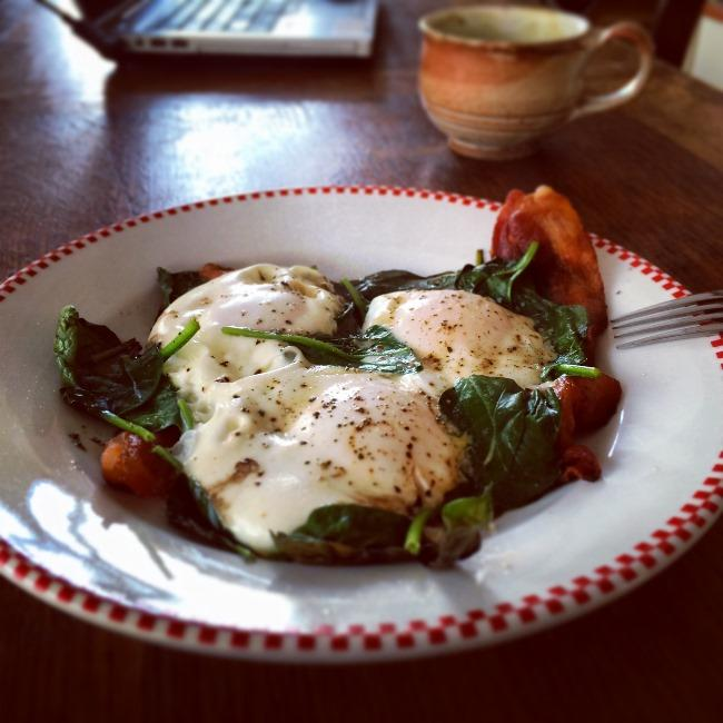 Slow carb breakfast of bacon and eggs baked on top of a bed of spinach