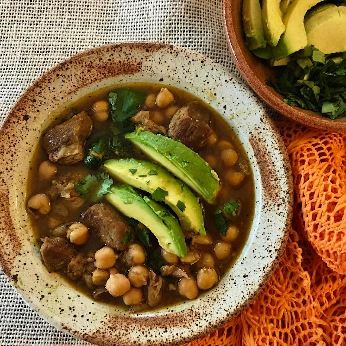 Bowl of pork posole with garbanzo beans and sliced avocado garnish