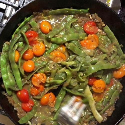 Romano beans and cherry tomatoes in a skillet saute