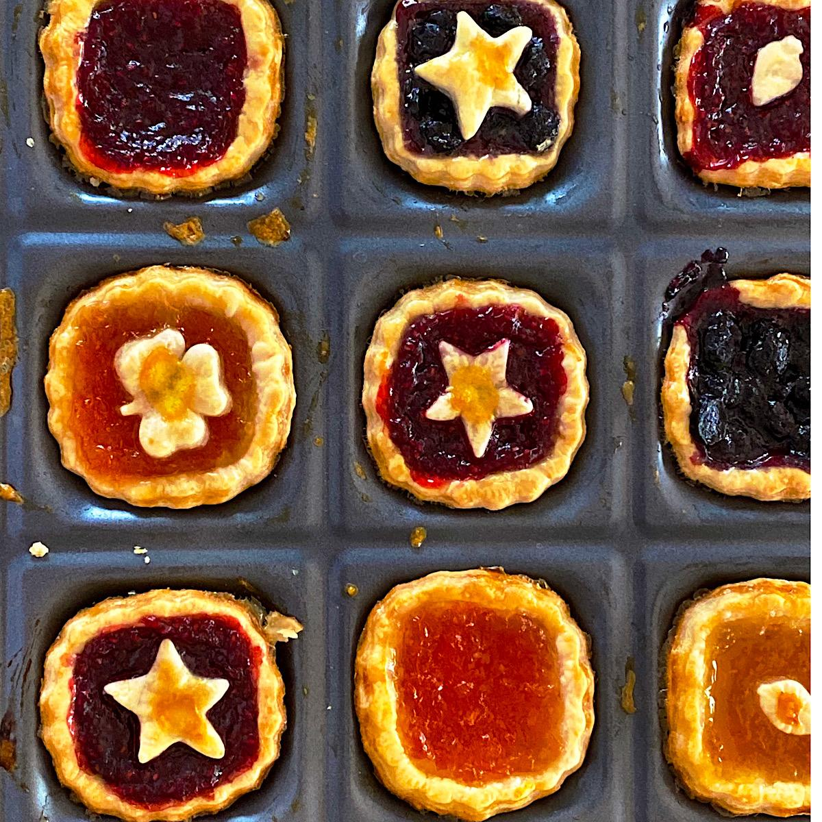 9 jam tarts in a baking tin made with pie dough and great jam