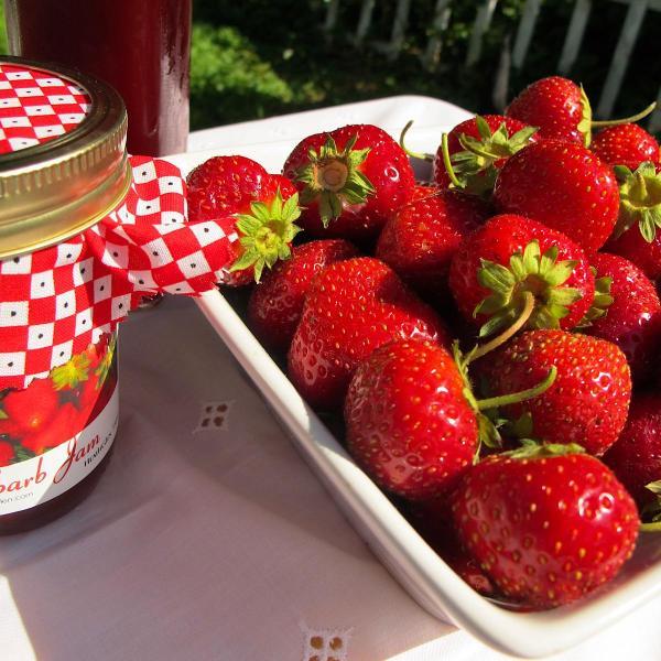 Bowl of fresh strawberries and a jar of strawberry rhubarb jam
