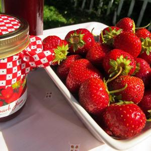 Bowl of fresh strawberries and a jar of strawberry rhubarb jam