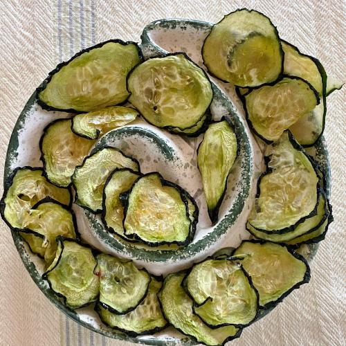 Dish of salt and vinegar cucumber chips dried in dehydrator