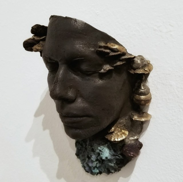 The mask cast in bronze and patinaed