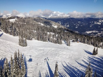The gondola's shadow sits in majestic scenery, a group a skiers barely visible.