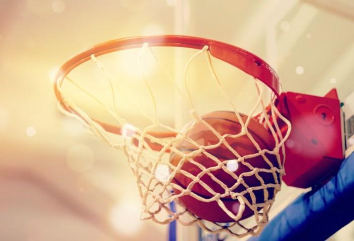Orange basketball ball flying into the basketball hoop