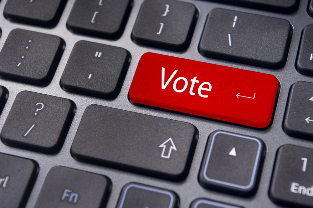 """vote or voting concepts, through computer or internet, with a """"Vote"""" message on red enter key of keyboard."""