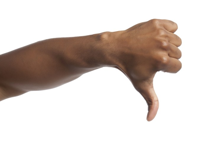 Close-up image of human hand with thumbs down against the white surface