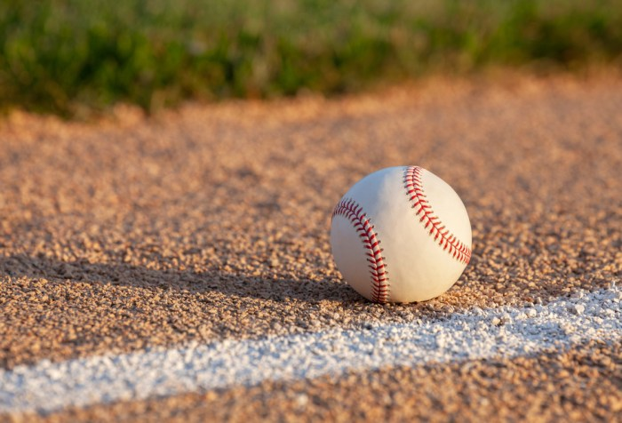 Low angle selective focus view of a baseball on a basepath with a white stripe