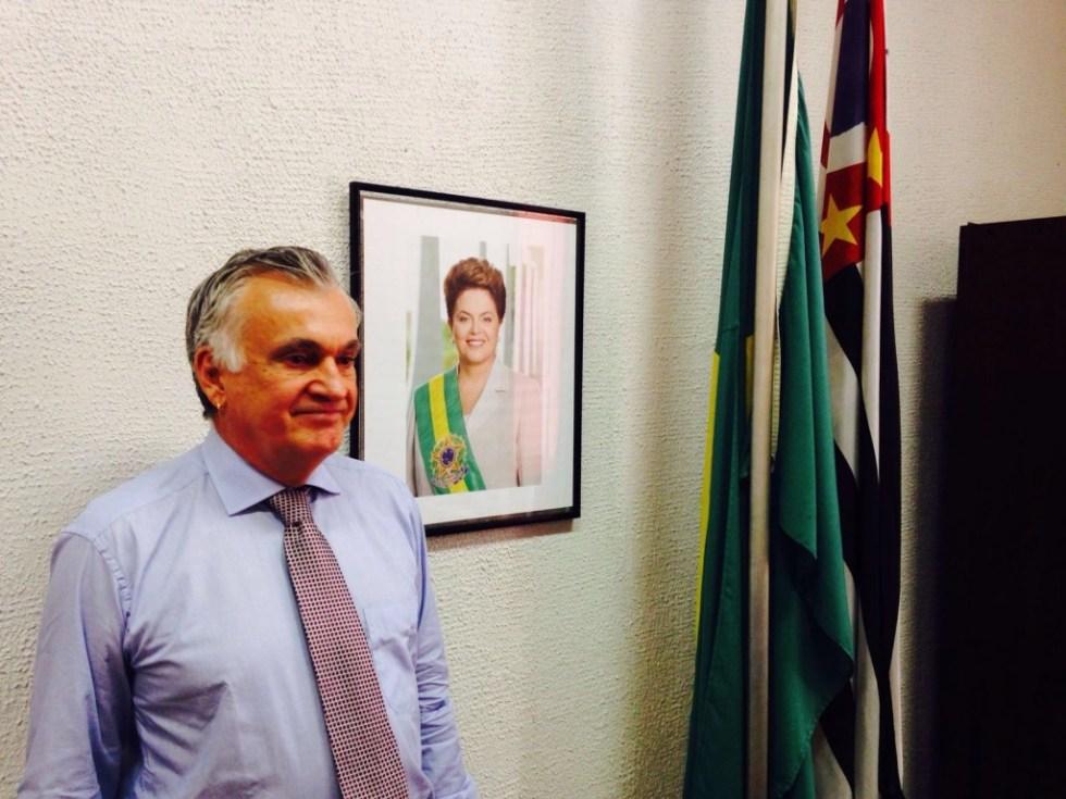 Juca Ferreira posa diante da fotografia oficial da chefa, na sede paulistana da Funarte - foto Jotabê Medeiros