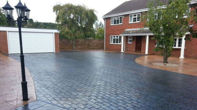 grey imprinted concrete driveway with brown imprinted concrete surround in Kent