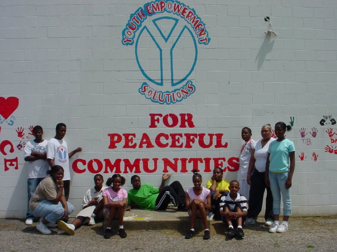 A photo of one of the Youth Empowerment Solutions (YES) cohorts in front of a mural titled For Peaceful Communities that they painted. The YES Curriculum was informed by data from FAS.