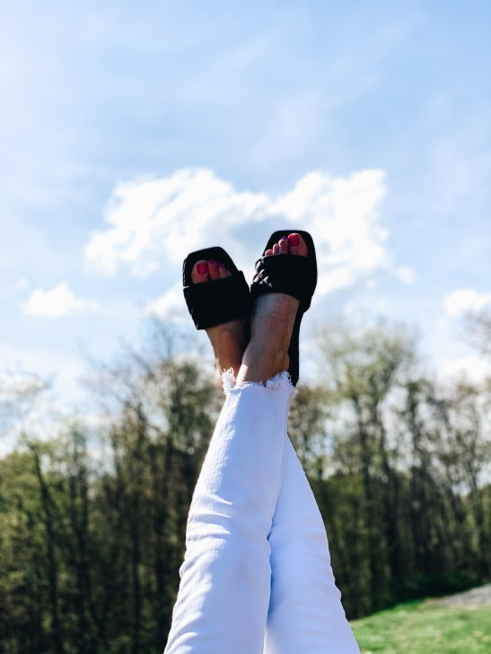 Top 7 Cute Spring Sandals for Women featured by top Pittsburgh fashion blogger, Fashionably Late Mom.  Spring Sandals by popular Pittsburgh fashion blog, Fashionably Late Mom: image of a woman wearing a pair of black slide sandals.