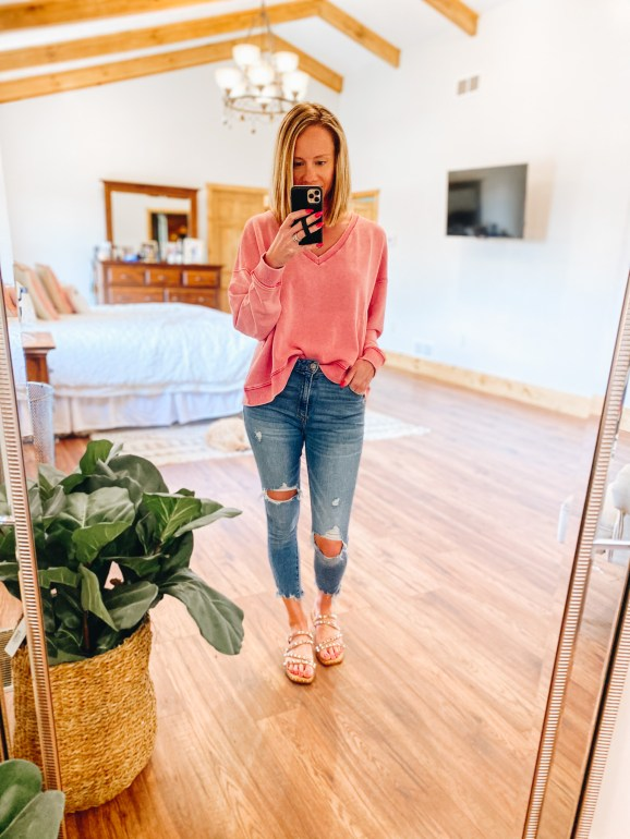 Top 7 Cute Spring Sandals for Women featured by top Pittsburgh fashion blogger, Fashionably Late Mom.  Spring Sandals by popular Pittsburgh fashion blog, Fashionably Late Mom: image of a woman wearing a pink v-neck sweatshirt, deconstructed denim, and slide sandals.