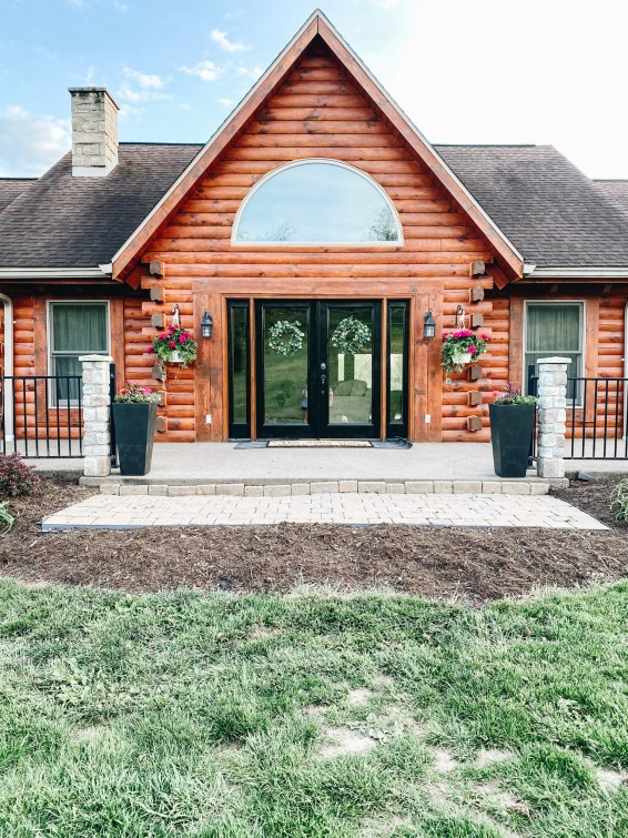 after a front porch refresh | Summer Front Porch by popular Pittsburg life and style blog, Fashionably Late Mom: after image of a front porch on a log home with black frame doors, black planters with pink flowers, hanging potted pink flower planters, and greenery wreaths.