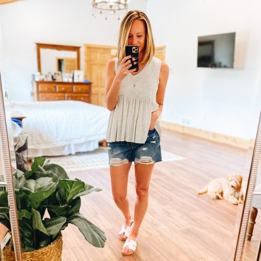 Pink Lily Boutique Favorites for Spring and Summer featured by top Pittsburgh fashion blogger, Fashionably Late Mom |  Pink Lily Boutique by popular Pittsburg fashion blog, Fashionably Late Mom: image of a woman wearing a Pink Lily Boutique grey peplum tank, deconstructed jean shorts and white strap slide sandals.
